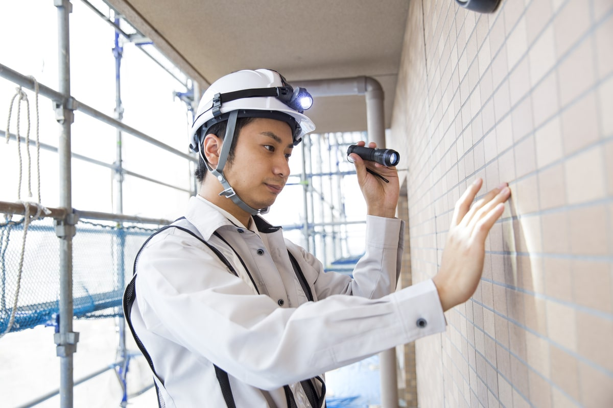 一人の作業員が壁を点検している様子
