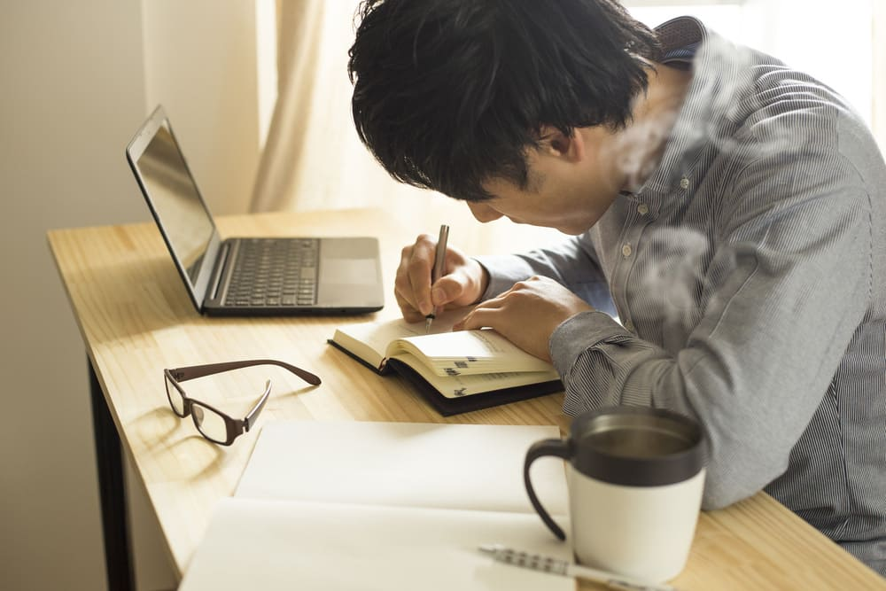 男性がノートに何か書いている写真